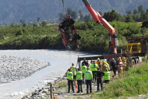 Police use a crane to recover the car from the river.
