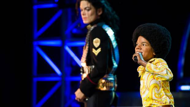 UNREAL: A performer, in yellow, on stage beside the Madame Tussaud's waxwork version of Michael Jackson.