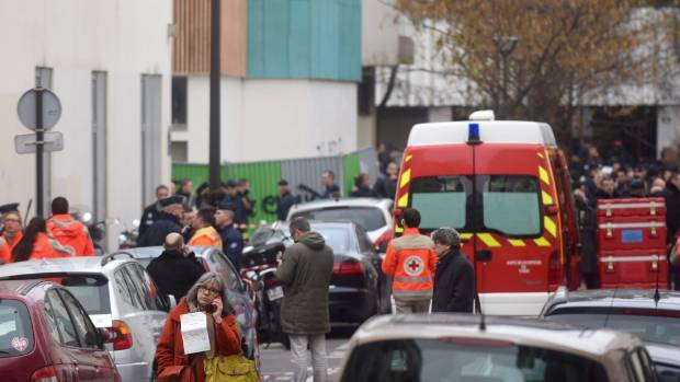 BRUTAL ATTACK: A survivor talks on her mobile phone (foreground) as police and emergency services take control of the ...