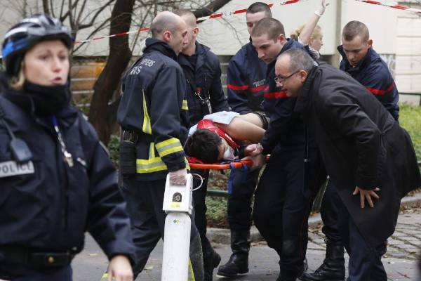 Firefighters carry a victim on a stretcher at the scene after masked gunmen stormed the offices of Charlie Hebdo, a ...