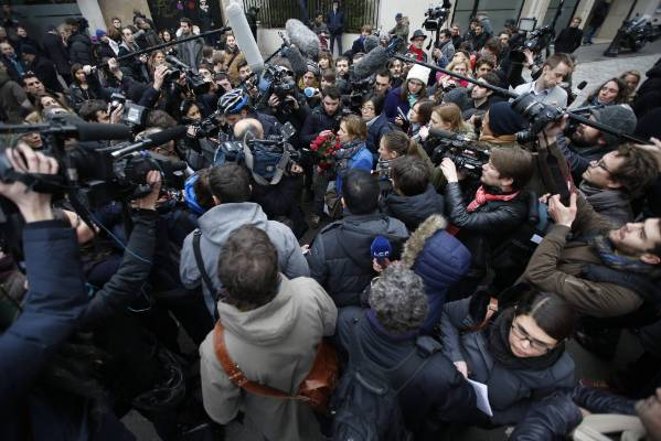 A woman with a bouquet of roses is surrounded by journalists as she arrives at the scene after a shooting at the Paris ...