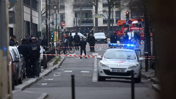 CLAMPDOWN: Ambulances and police officers gather in front of the offices of the French satirical newspaper Charlie Hebdo .