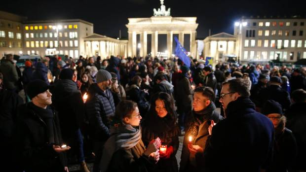 GLOBAL MOURNING: People gather to mourn for the victims in front of the Brandenburg Gate near the French embassy in Berlin.