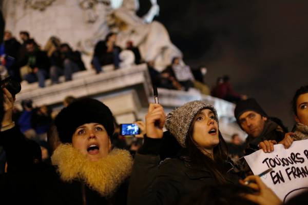 A woman holds a placard in Paris at Republique square during a vigil to pay tribute to the victims of the shooting at ...