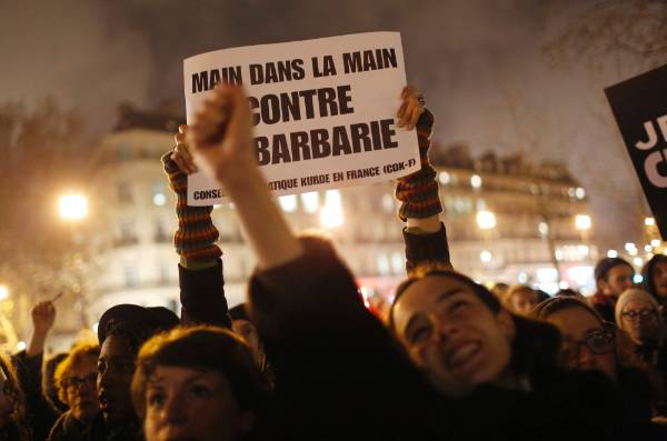 """A woman holds a placard that reads """"Hand in hand against barbarity,"""" during a vigil to pay tribute to the victims of the ..."""