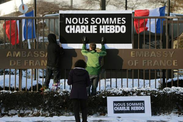 "WASHINGTON DC: A sign reading ""We are all Charlie Hebdo"" is raised at the French Embassy."