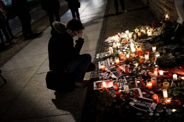 BERLIN: A man kneels in front of the vigil at Berlin's French Embassy.