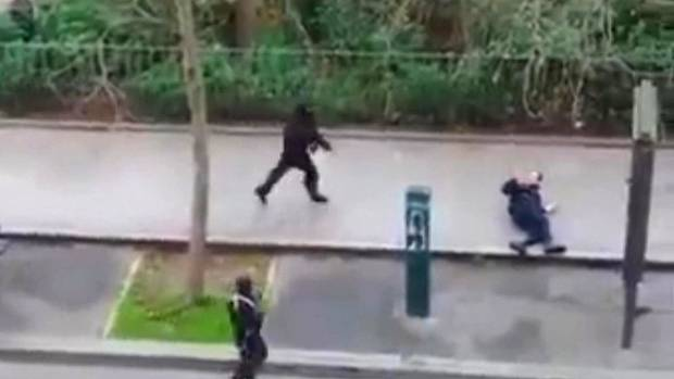 NO MERCY: The gunmen approach a police officer squirming on the street, his arms raised, before shooting him at ...