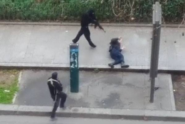Gunmen shoot a wounded police officer on the ground at point-blank range after fleeing the offices of Charlie Hebdo in ...