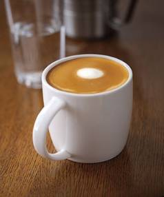 """THE AMERICAN OFFERING: """"Expertly steamed whole milk poured over two shots of espresso, topped with microfoam swirled ..."""
