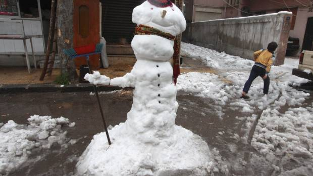 A snowman stands on the streets of Damascus, Syria, following storms that hit the Middle East.