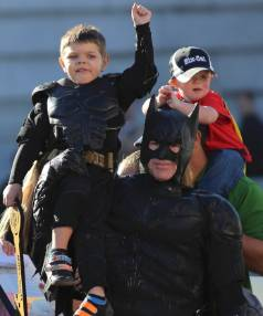"""Five-year-old leukemia survivor Miles Scott, dressed as """"Batkid"""" waves to crowd on the shopulders of Batman during a ..."""