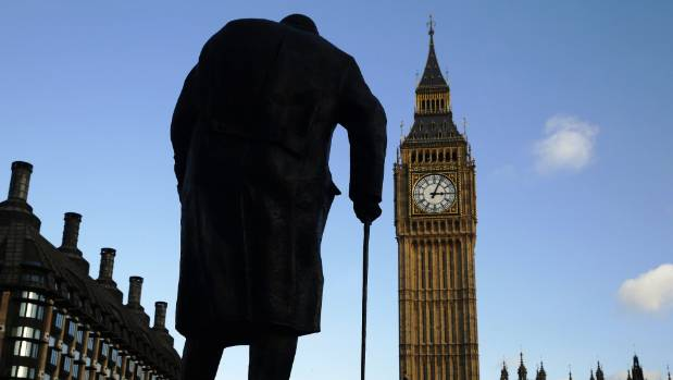 The statue of Britain's former Prime Minister Winston Churchill is silhouetted in front of the Houses of Parliament in ...