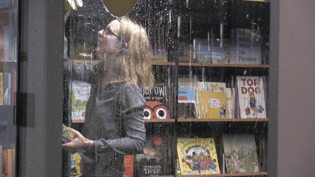 CLEAN UP: A staff member at Unity Books on Willis St in Wellington rescues books after the store was flooded by a burst pipe.