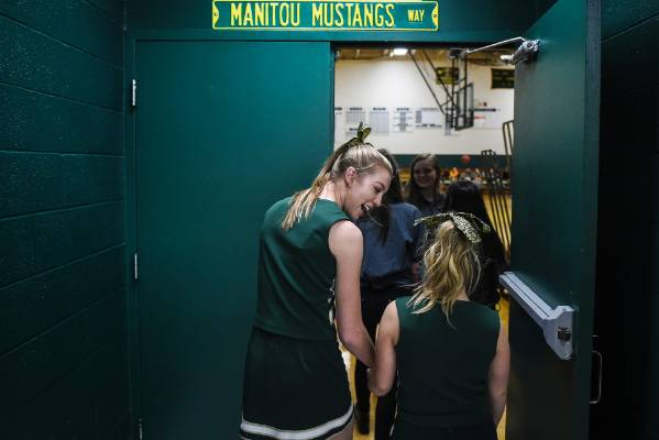 Manitou Springs cheerleader Kelsey Hartwig, left, holds hands with sophomore cheerleader Kory Mitchell, who was born ...