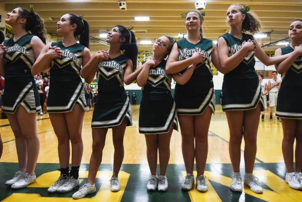 Manitou Springs sophomore Kory Mitchell, center, who was born with Down syndrome, rests her head on the shoulder of ...