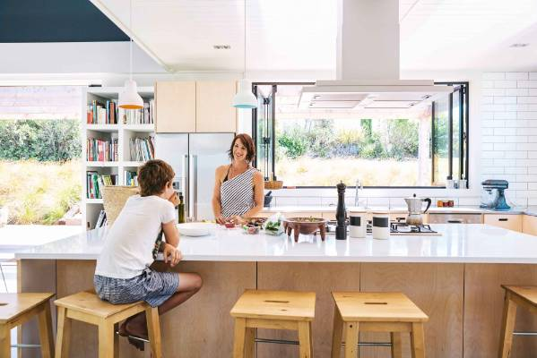 LIGHT & BRIGHT: Jai and Ana at the long breakfast bar in the kitchen which has side-by-side Bosch ovens, shelves of ...