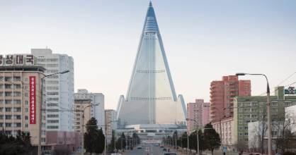 City centre of Pyongyang with skyscraper and traffic. The Ryugyong hotel has sat, unfinished, for almost three decades. ...