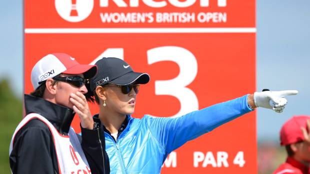 Duncan French and Michelle Wie plot their way to another green.