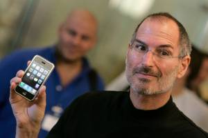 Former Apple chief executive Steve Jobs holds the original iPhone.