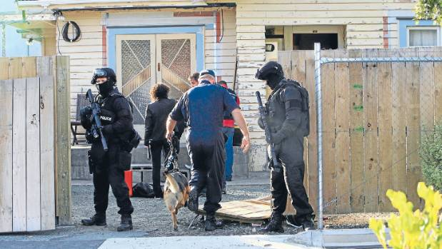 DRUG BUST: Armed police stand guard outside a Red Devils pad in Nelson during a raid at the conclusion of Operation ...