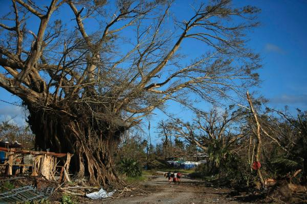 People walk through a street in Lenakel town after Cyclone Pam in Tanna,Vanuatu.