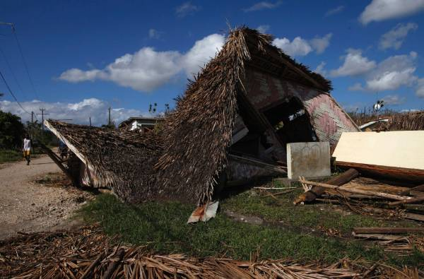 A man passes a destroyed house after Cyclone Pam struck in Lenakel, Tanna, Vanuatu.