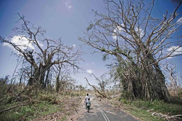 Children walk down a devastated main road on north side of the main island of Efate.