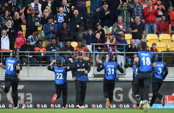 FROM ALL CORNERS: Black Caps players run to congratulate Daniel Vettori on his catch to dismiss West Indies batsman ...