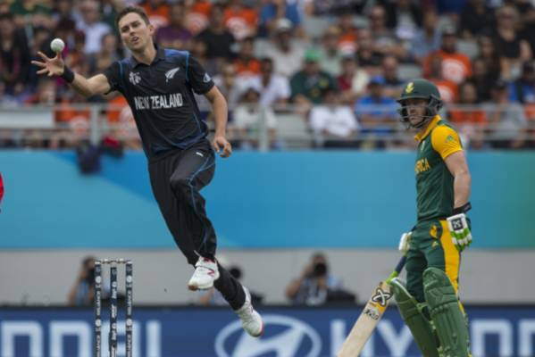 Trent Boult leaps to field the ball off his own bowling.
