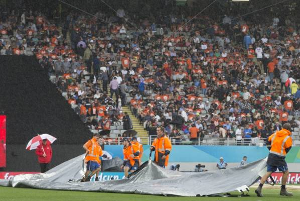 Eden Park grounds crew pull out the covers as rain falls.