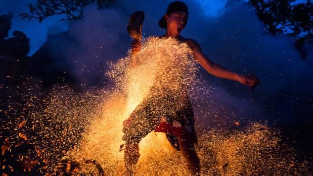 "A Balinese man kicks up the fire during the ""Mesabatan Api"" ritual ahead of Nyepi Day."