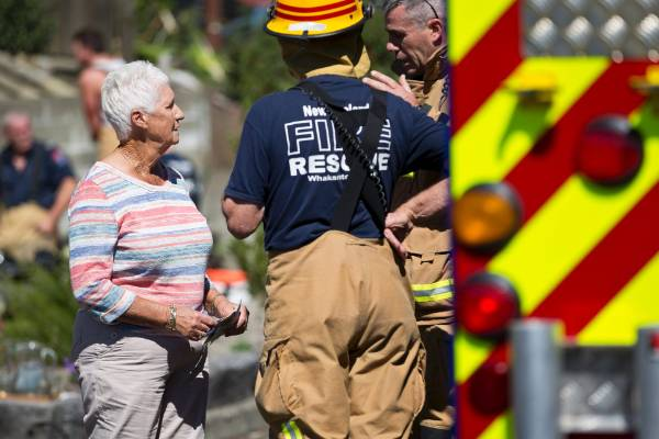 Lesley Morris speaks with firefighters after she and her husband Leslie managed to escape a fire at their home in Stoke.