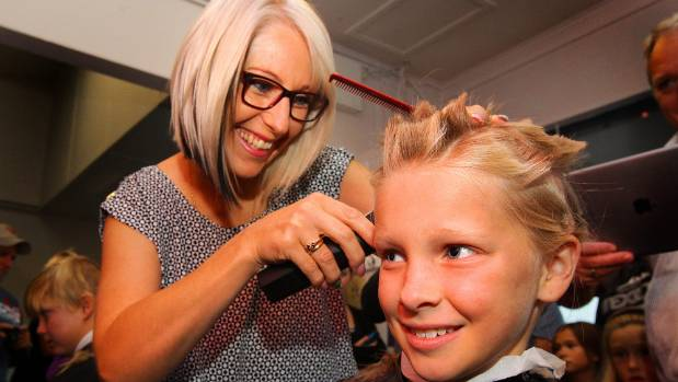 Sara Knowles, left, cuts 9 year old daughter Jessica's hair off for the Shave for a Cure week.