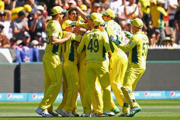 Mitchell Starc of Australia is congratulated by teammates after getting the wicket of Brendon McCullum of New Zealand ...