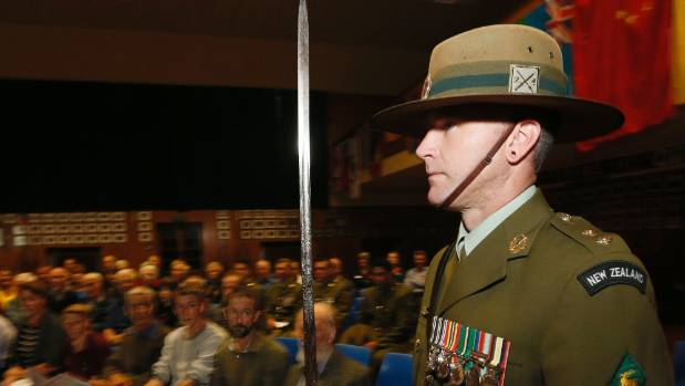 New Zealand Army reserve soldier Adam Friend carries the regimental sword used by Colonel Cyprian Brereton into the hall ...