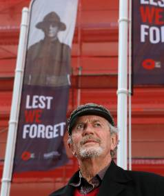 Brian Smythe poses under an ANZAC banner featuring his grandfather Hugh Bridge's portrait. Bridge is one of four ...