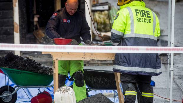 Fire Service personnel sieve through debris from the Collingwood Street house fire which claimed the lives of three people.