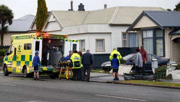 A pedestrian is put in the back of an ambulance after being hit by a car which also took out a fence on College Rd.