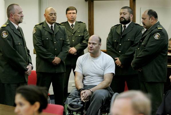 Graeme Burton, in a wheelchair, is surrounded by guards at Wellington High Court during his sentencing in April 2007.