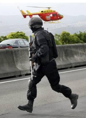 An Armed Offenders Squad member searches for killer Graeme Burton on Wainuiomata Hill Rd.