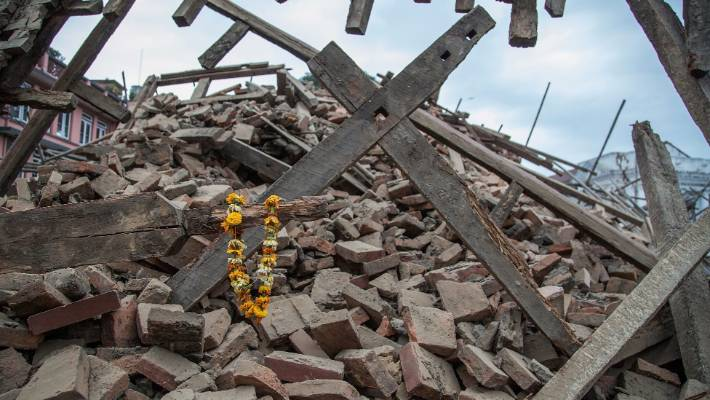d1b64578ced Flowers are left by survivors on top of debris from a collapsed building in  Kathmandu
