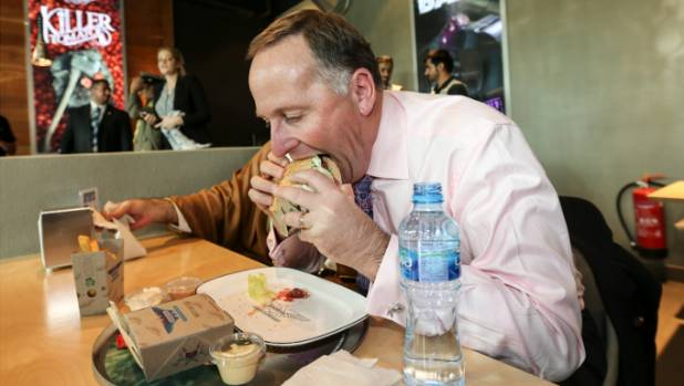 Prime Minister John Key tucks into a burger from New Zealand company, Burger Fuel, in Kuwait.