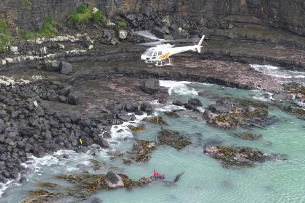 A salvage helicopter with rope attached to car wreck in Blue Cod Bay near Curio Bay.