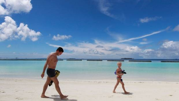 A tourist walks with a girl on the beach at Kurumba Resort on Vihamanafushi island.