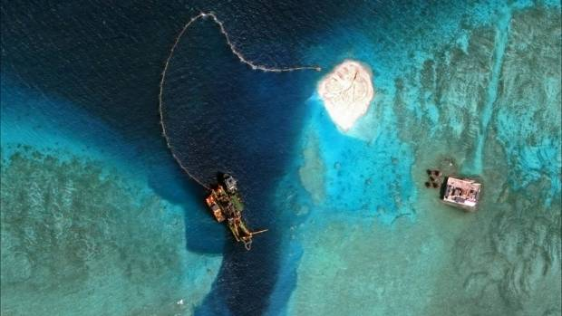 A dredger operates on Mischief Reef, located 216 km west of the Philippine island of Palawan. This satellite image was ...