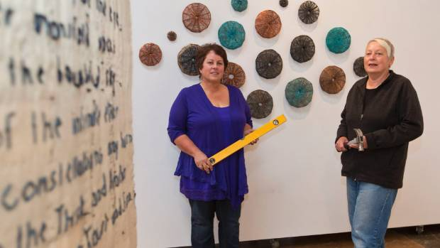 Ronnie Martin, left and Jo Kinross installing works for the Changing Threads - Contemporary Fibre Art Awards at the ...