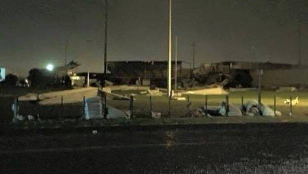 Roofing iron from Bay Park lays strewn through a fence following the tornado.