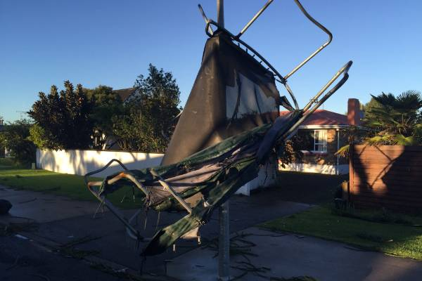 A trampoline wrapped around a streetlight after being flung in the air by Tauranga's tornado.
