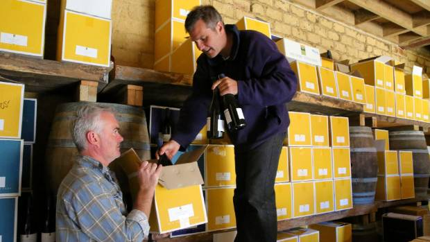 Simon McGuire, left, and Todd Stevens unpacking older vintages in the mudbrick library.